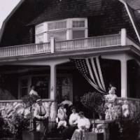 Black and white antique photo of family sitting on covered front porch of two story home